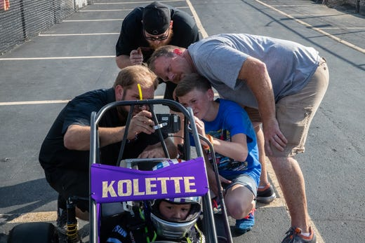 Kolette waits patiently as a group of guys, including her father, Anthony, and her friend, Ryan, attempt to figure out the settings on a device that shows her speed and other technical details on her quarter midget race car during practice at Indy Mini Speedway at the Indiana State Fairgrounds on Tuesday, Oct. 1, 2019.