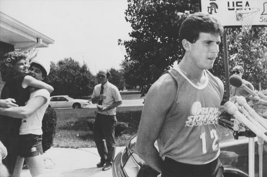 June 22, 1987: Steve Alford addresses questions about being passed over in the first round of the NBA draft while behind him, his fiance Tanya and brother Sean celebrate him being chosen by the Dallas Mavericks. They were outside the Alford home in New Castle.
