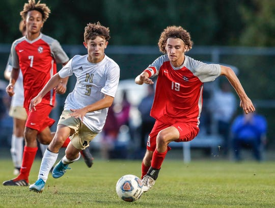Noblesville forward Spencer Holland (5) and Fishers midfielder Reese May (19) battle for the ball, Wednesday, Oct. 9, 2019, Noblesville, Ind. Noblesville defeated Fishers, 3-1 to advance to the sectional championship.