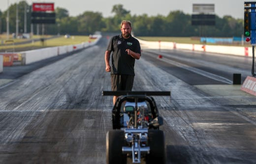 Anthony Dicero helps direct and straighten his daughter, Kolette, in her junior dragster before a practice run at Lucas Oil Raceway on Wednesday, Aug. 7, 2019.