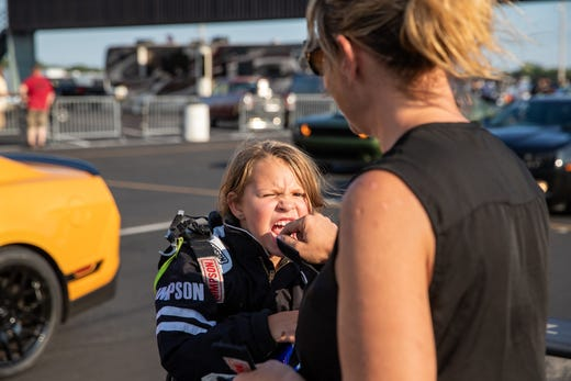 Jess Dicero checks a wiggly tooth for her daughter, Kolette, after Kolette's first test run down the strip at Lucas Oil Raceway on Wednesday, Aug. 7, 2019.