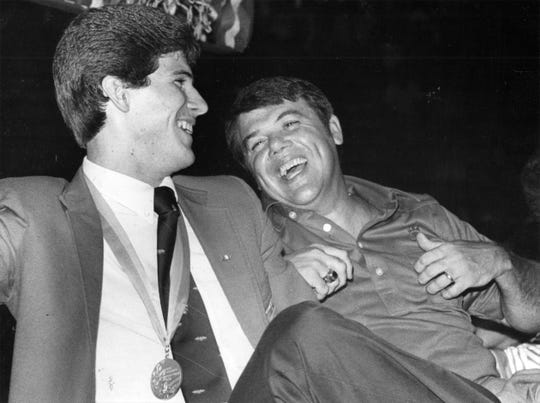 August 1984: Steve Alford and his father, Sam, celebrate his Olympic victory at the New Castle High School gym. Steve later took off his gold medal and hung it around his father's neck.