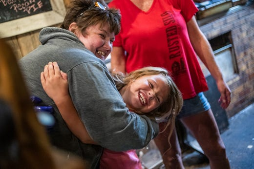 Kolette Dicero gets a hug from all of the Rusted Silo employees after a sponsorship meeting with owner Rob Ecker on Wednesday, Sept. 18, 2019. Dicero, mid meeting, grabbed a pair of gloves, went into the kitchen, and helped prepare her family's meal.