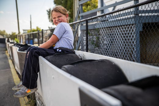 "Kolette Dicero, 7, of Pittsboro, Ind., takes a break from practice and sits on the railing at Indy Mini Speedway at the Indiana State Fairgrounds on Tuesday, Oct. 1, 2019. Dicero, who drives both a quarter midget and a junior dragster, started racing at age five. ""I want to win a trophy and just have fun and just go race,"" she says. ""And I don't care about anything other."""