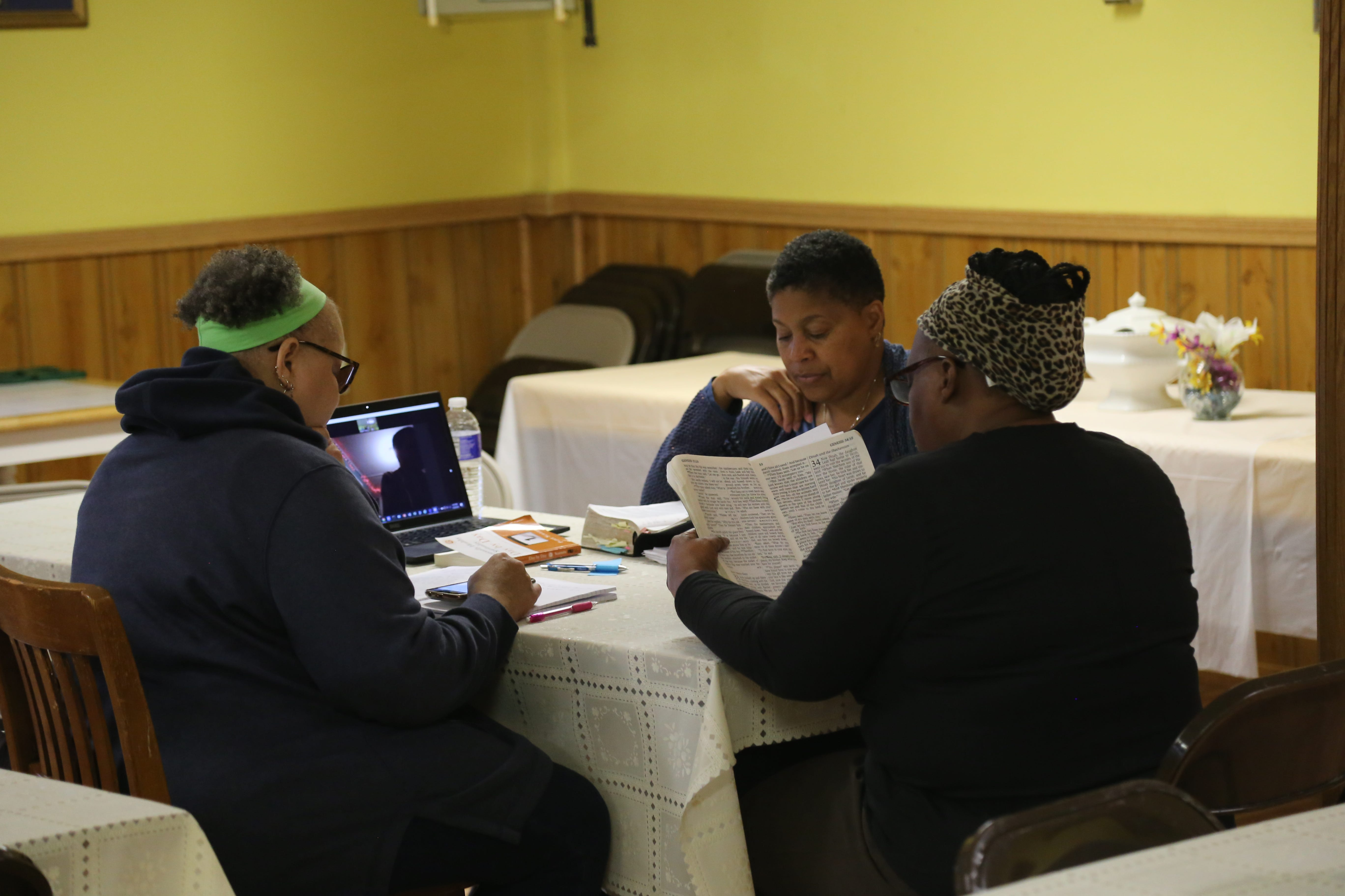 Rev. Paris Price (back) leads parishioners in a bible study class inside  a room in St. James AME Zion Church on the evening of Wednesday, Oct. 9.