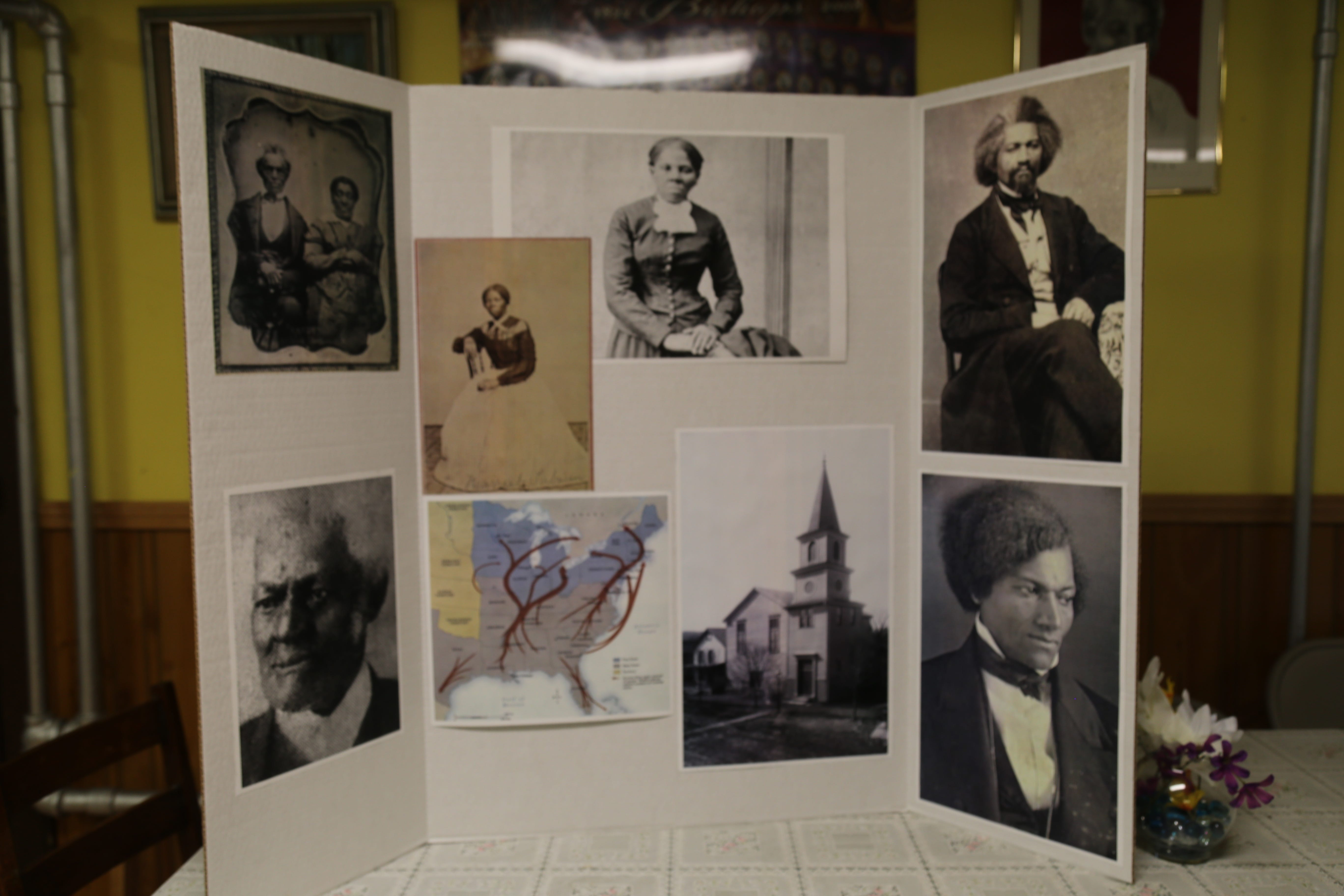 A poster board showing photos of Harriet Tubman and Frederick Douglass  stands on a table in a room in St. James AME Zion Church in Ithaca, N.Y. Both abolitionists visited and gave speeches at the church.