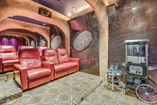 Le Triomphe golf course mansion, on the market for $650,000, has an elaborate movie theater, full outdoor kitchen, three fireplaces, pool and spa with a spiral staircase to the upper deck.