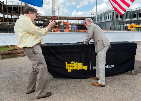 Larry Sides photographs Airport Commissioner Paul Segura as he signs the final beam to be installed as the Lafayette Regional Airport  officials hold ceremony to mark the end of steel infrastructure for the new terminal Thursday, Oct. 10, 2019.