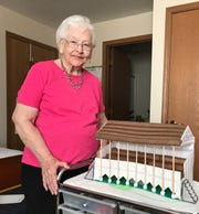 Norma Hite, 92, stands beside the model of the old grandstand at the Fairfield County Fairgrounds she recently completed with yarn and plastic. She used only her memories and a photo of the grandstand as her guide. Fire destroyed the actual grandstand in 2016.