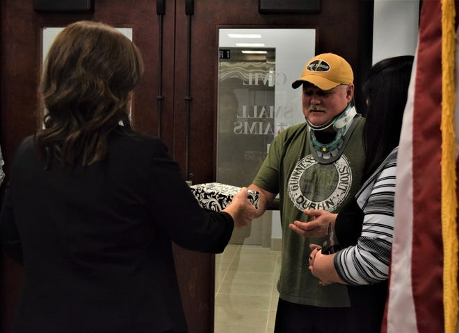 John and Donna Williamson, right, accept a donation from Valeda Slone, the clerk of courts for the Fairfield County Municipal Court. John, a Fairfield County Sheriff's deputy, was injured in a high-speed pursuit in September.