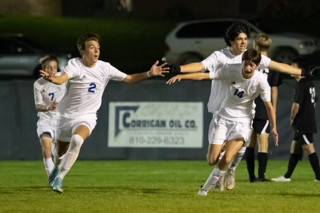 Detroit Catholic Central soccer players celebrate a goal by Vincent Stockton (2) with 2:23 left in the second overtime of a 1-0 first-round district victory over Brighton on Wednesday, Oct. 9, 2019.
