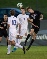 Brighton's Josh Adam (26) and Detroit Catholic Central's Clay Moscovic (7) battle for a ball in the air in a first-round district soccer game on Wednesday, Oct. 9, 2019.