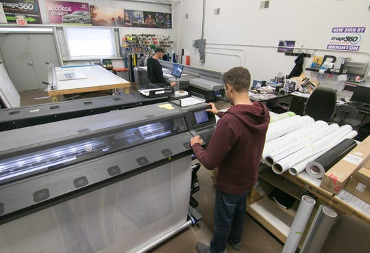 Eric Curry, in the background, and Chad Leonard run large format printers at image360 in Genoa Twp. Thursday, Oct. 10, 2019.