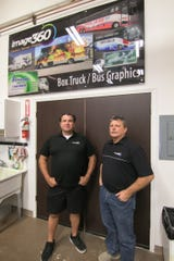 """image360's Joe Agius, the visual communication and marketing specialist, left, and owner John Nagel, shown Thursday, Oct. 10, 2019, stand under a sample of their signage products, which shows wraps applied to buses used in a """"Transformers"""" movie."""