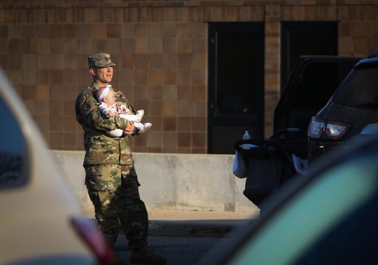 Michigan National Guard Sgt. 1st Class Leonard Adams holds 18-month-old daughter Amelia, Thursday, Oct. 10, 2019, at the Army Aviation Facility in Grand Ledge. Adams and about 80 fellow Michigan Army National Guard members will deploy to the Middle East as part of combat operations against ISIS and other terrorist organizations.