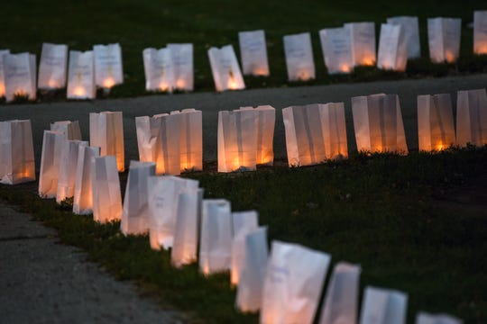 Luminarias light up the sidewalk on Thursday, Oct. 10, 2019, outside the East Lansing Library. Parents of Sister Survivors Engage (POSSE) and The Army of Survivors lit more than 505 luminarias as a reminder of the effects of sexual abuse prior to Michigan State University President Samuel Stanley's meeting with Larry Nassar survivors inside the library.
