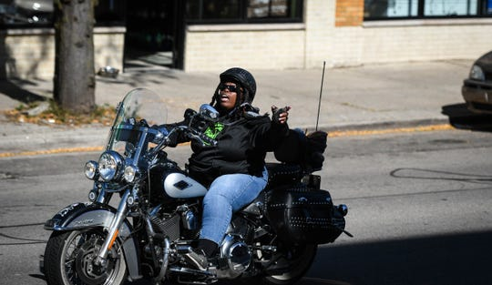 """Rose Cooper, 56, sings a version of the song """"Hallelujah"""" while riding her Harley-Davidson Heritage Softail down Michigan Avenue in Lansing on Tuesday, Oct. 8, 2019."""