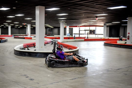 A patron races around the go-kart track at High Caliber Karting and Entertainment on Wednesday, Oct. 9, 2019, inside the Meridian Mall in Okemos.
