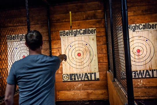 Steve Randolph throws an ax at a target at High Caliber Karting and Entertainment on Wednesday, Oct. 9, 2019, inside the Meridian Mall in Okemos. Randolph was at the business for a company team-building outing. Ax throwing is one of many activities offered at the business.