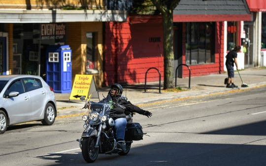 """Rose Cooper, 56, of Lansing  sings a version of the song """"Hallelujah"""" while riding her Harley-Davidson Heritage Softail down E. Michigan Avenue Tuesday afternoon, Oct. 8, 2019."""