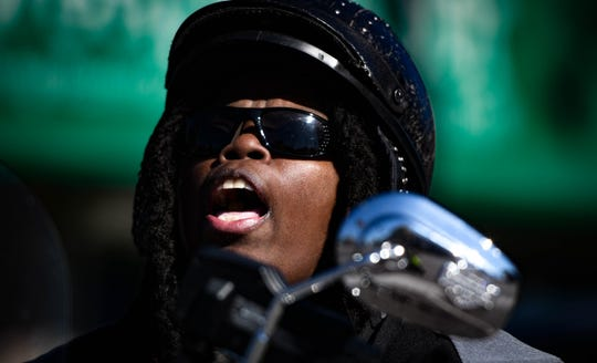 Rose Cooper, 56, of Lansing  belts out a gospel song while riding her Harley-Davidson Heritage Softail on Michigan Avenue Tuesday, Oct. 8, 2019.