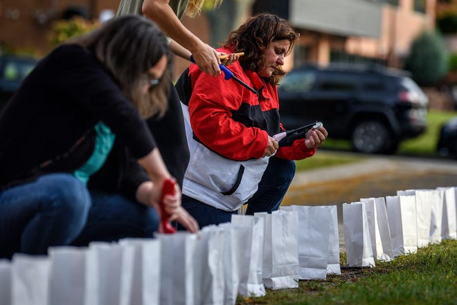 Angie Cosman, right, lights candles on Thursday, Oct. 10, 2019, outside the East Lansing Library. Parents of Sister Survivors Engage (POSSE) and The Army of Survivors lit more than 505 luminarias as a reminder of the effects of sexual abuse prior to Michigan State University President Samuel Stanley's meeting with Larry Nassar survivors inside the library.