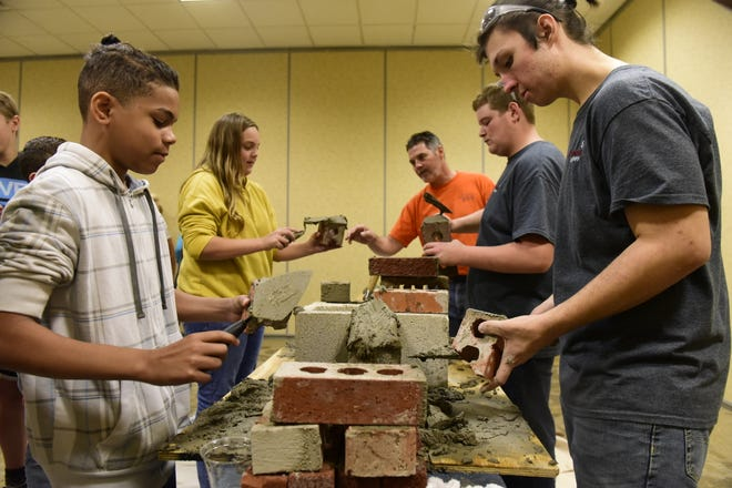 Students from Malabar Intermediate School learn tricks of the masonry trade Thursday at the Mid-Ohio Educational Service Center.