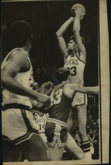 Lew Alcindor took his first shot and made his first basket for the Milwaukee Bucks in their National Basketball Association opener with the Detroit Pistons here Saturday afternoon. The 7 foot Alcindor jumped to get of a shot over Terry Dischinger (43) of the Pistons.