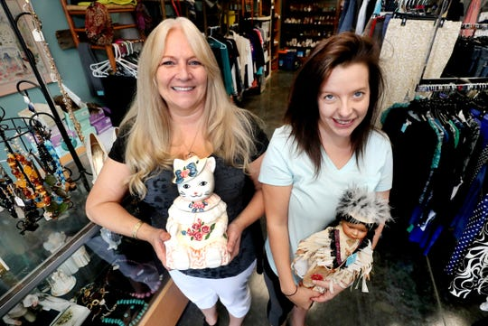 Kellie Vanderbloom, left, and Kayla Ellis, right, with The Happy Tails Fur-Ever thrift store hold some of the items for sale at the store. The thrift shop gives 100% of their profits back to support non-profit animal rescue organizations.