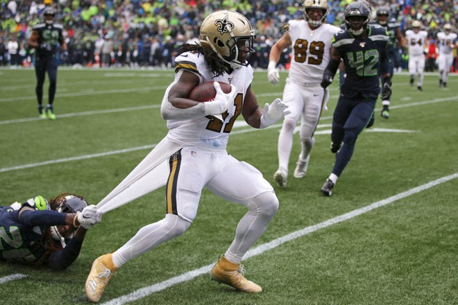 Seattle Seahawks' Shaquill Griffin, left, grabs hold of a piece of uniform as he tries to stop New Orleans Saints' Alvin Kamara on Sept. 22, 2019.
