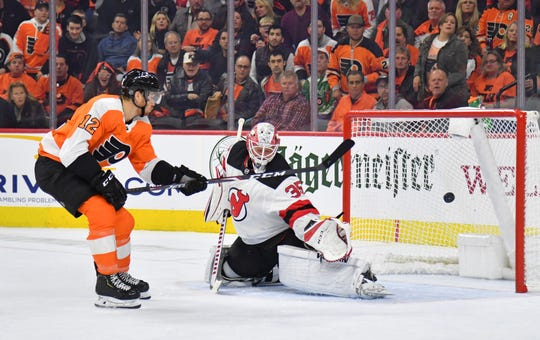 Oct 9, 2019; Philadelphia, PA, USA; New Jersey Devils goaltender Cory Schneider (35) makes a save against Philadelphia Flyers left wing Michael Raffl (12) during the second period  at Wells Fargo Center.