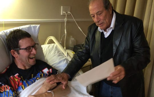 """""""Sopranos"""" actor Dan Grimaldi gives Mike Lowe, a Washington Township man with ALS, an autographed photo during a surprise visit at Oradell's Care One facility on Oct. 9."""