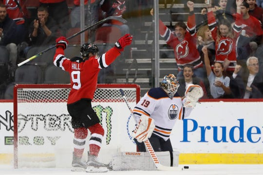 New Jersey Devils left wing Taylor Hall (9) celebrates a goal by Kyle Palmieri, in front of Edmonton Oilers goaltender Mikko Koskinen (19) during the first period of an NHL hockey game Thursday, Oct. 10, 2019, in Newark, NJ.