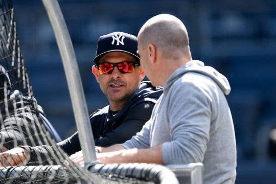New York Yankees manager Aaron Boone, left, and general manager Brian Cashman talk during the team workout on Thursday, Oct. 10, 2019, in the Bronx.