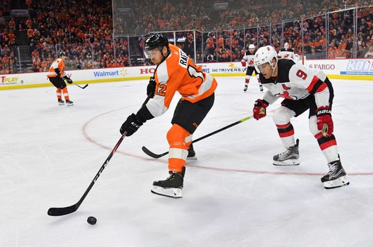 Oct 9, 2019; Philadelphia, PA, USA; Philadelphia Flyers left wing Michael Raffl (12) controls the puck against New Jersey Devils left wing Taylor Hall (9) during the second period at Wells Fargo Center.
