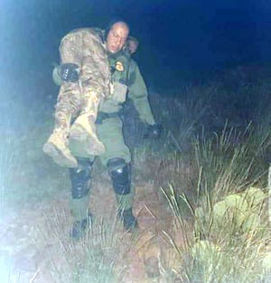 A U.S. Border Patrol agent brings Chris Archibeque off the Florida Mountains during a rescue on Saturday south of Deming, NM.