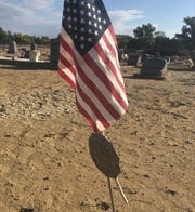 An American Legion stake with a flag on it is seen, Thursday, Oct. 10, 2019, at Lewis Allinger's grave in the Aztec Cemetery.