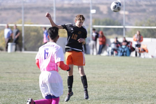 Aztec's Kolton Bruhn takes a shot on a header against Bloomfield during Thursday's boys soccer match at the Aztec Tiger Sports Complex.
