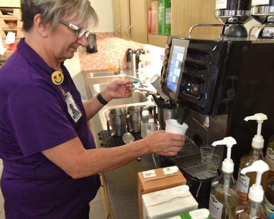 Read a Latte Cafe manager Cheryl Dingeldey makes a latte using Starbucks products and an automatic coffee dispenser.