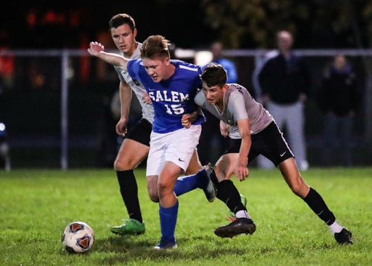 Salem's Luke Benford fights for the ball against Plymouth.