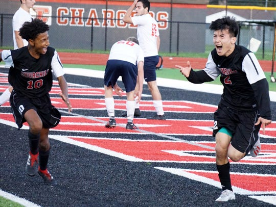 Churchill Charger Sadat Adel, right, begins to celebrate his late first-half goal with teammate Daniel Jakubowski, left, trying to catch up to the celebratory teammate.