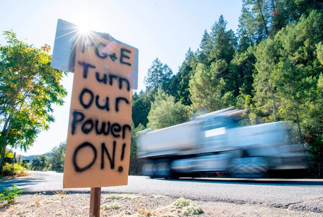 A sign calling for PG&E to turn the power back on is seen on the side of the road during a statewide blackout in Calistoga, California, on October, 10, 2019. Photo by JOSH EDELSON/AFP via Getty Images