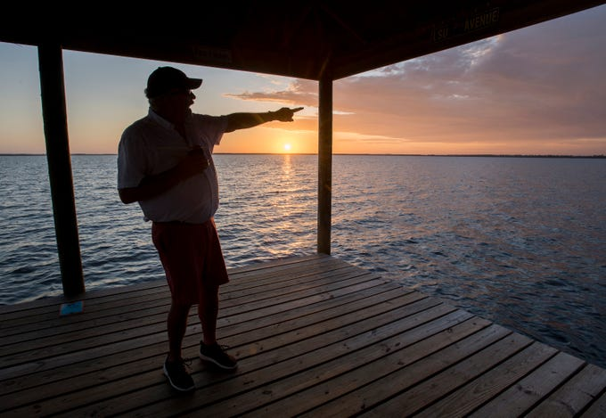 Ramsey Beach community resident Steve Swiler points out the location of International Paper while standing on his dock on Perdido Bay in Pensacola on Wednesday, Oct. 9, 2019.