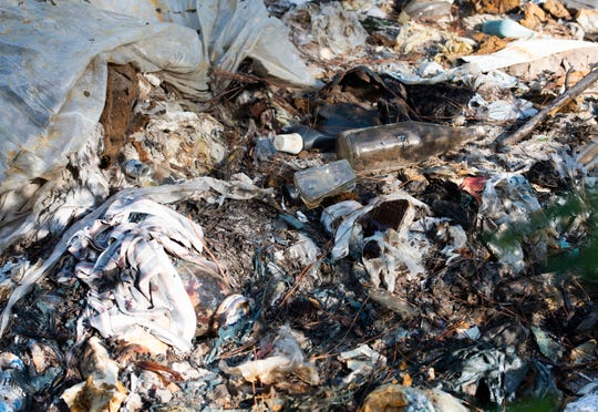 Trash contaminates the property of Abbey and Jeff Rodamaker on Oct. 9, 2019. The couple bought six acres of secluded land off of U.S. 98 to build their dream home only to discover it was once used as a landfill.
