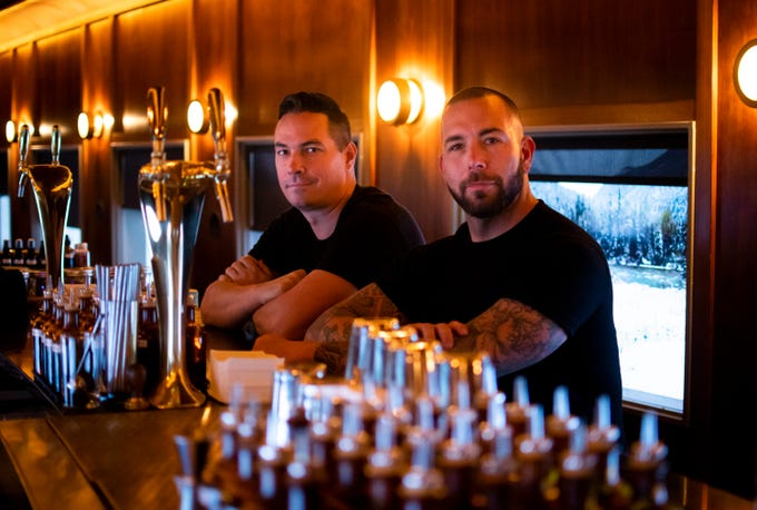 Jason Asher, right, and Rich Furnari pose at the bar in the train car section of Century Grand before opening on Thursday, Oct. 10, 2019.