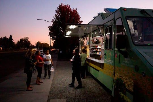 Los residentes locales recogen comidas del camión de comida El Coyote, uno de los pocos camiones de comida abiertos en el área, en Sonoma, California, el 9 de octubre de 2019, después de que la compañía de servicios públicos Pacific Gas & Electric (PG&E) comenzara los cortes de energía planificados.