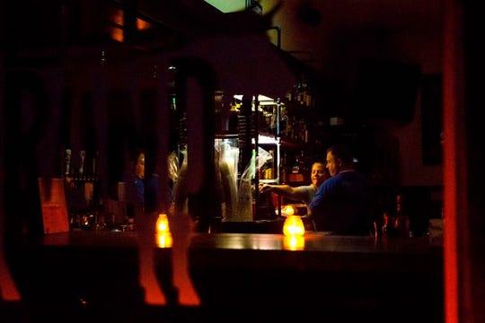 Los propietarios de restaurantes Emily Schiffman y Kevin Dress usan la luz de las velas y una linterna mientras se preparan para cerrar Reel and Brand en Sonoma, California, el 9 de octubre de 2019, después de que la compañía de servicios públicos Pacific Gas & Electric (PG&E) comenzara los apagones planeados.