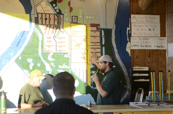 Michigan Department of Natural Resources Wildlife Technician John Darling, right, explains the lottery selection process used at St. Clair Flats State Wildlife Area on Oct. 8, 2019, on Harsens Island.