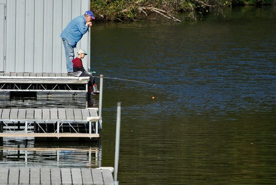 """John Repp of New Freedom looks on as his grandson Asher Lawrence, 8, waits for a bite while fishing from the docks at Lake Redman, Thursday, October 10, 2019. """"I haven't fished in 65 years,"""" said Repp."""