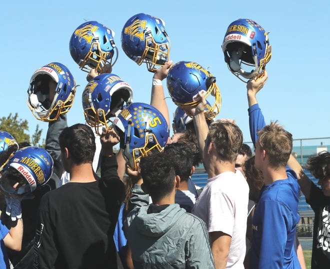 Anderson High School football players give a helmet salute at the end of their practice on Thursday, Oct. 10, 2019.